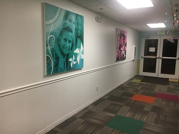 Big corporate art of kids in hall - green color