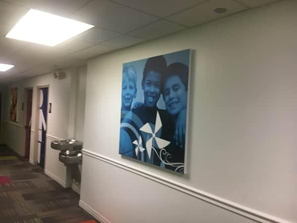 Big corporate art of three boys in hall